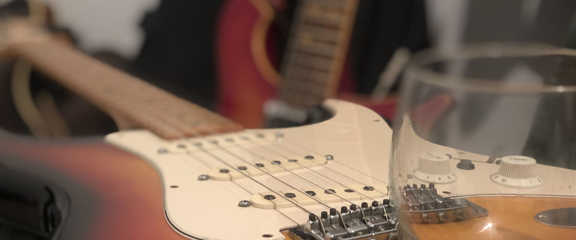 Picture shows a whiskey glass on a electric guitar's body. You can spot fender stratocaster and rickenbacker 620